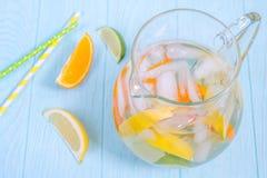 Broc de limonade avec le citron, orange, tranches de chaux Photos stock