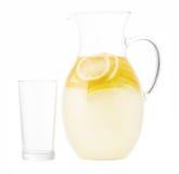 Broc de limonade avec les tranches de citron et le verre vide d'isolement dessus Photographie stock libre de droits