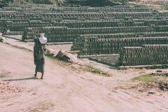 broc de transport de personne aux pieds nus de pauvres sur l'épaule et l'entrepôt extérieur des briques autour photographie stock