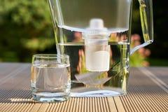 Broc en plastique de filtre d'eau et un verre propre d'une fin claire de l'eau sur le fond de jardin d'été photos libres de droits
