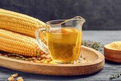 Broc en verre avec l'huile de maïs photos stock