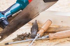 Broca com madeira, chaves de fenda e parafusos Foto de Stock