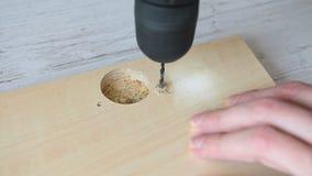 Broca elétrica que perfura um furo na madeira filme