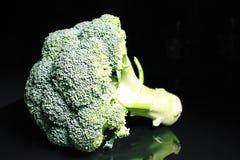 brocaded Grön hel broccoli på svart reflekterande studiobakgrund den svarta skinande spegeln avspeglade bakgrund för varje Co Arkivfoton
