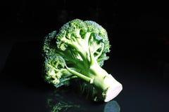 brocaded Grön hel broccoli på svart reflekterande studiobakgrund den svarta skinande spegeln avspeglade bakgrund för varje Co Royaltyfri Foto