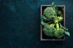 brocaded Ny grön broccoli på en svartstentabell arkivfoto