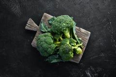brocaded Ny grön broccoli på en svartstentabell royaltyfria bilder