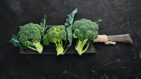 brocaded Ny grön broccoli på en svartstentabell royaltyfri foto