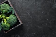 brocaded Ny grön broccoli på en svartstentabell royaltyfri bild