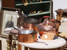 Brocante. Display of old copper cookware. Background of old photo frames, lamps and antique furniture Royalty Free Stock Photo