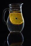 Brocca con acqua ed una fetta di arancia Fotografia Stock Libera da Diritti