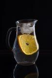 Brocca con acqua, ghiaccio e l'arancia su fondo nero Fotografia Stock Libera da Diritti