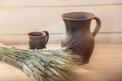 Brocca dell'argilla e una tazza sulla tavola Immagini Stock Libere da Diritti