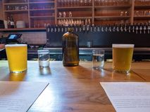 Brocca di acqua, tazze, birra, menu del brunch sul contatore della barra Fotografia Stock Libera da Diritti