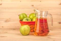 Brocca di succo e di mele di mele su un fondo di legno Fotografie Stock Libere da Diritti