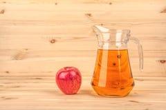 Brocca di succo e di mele di mele su un fondo di legno Fotografia Stock