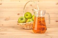Brocca di succo e di mele di mele su un fondo di legno Immagine Stock