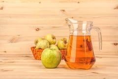 Brocca di succo e di mele di mele su un fondo di legno Immagini Stock