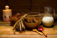 Brocca di vetro con latte, tazza con latte, una pagnotta del pane di segale, orecchie Immagini Stock Libere da Diritti