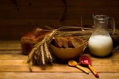 Brocca di vetro con latte, tazza con latte, una pagnotta del pane di segale, orecchie Fotografia Stock Libera da Diritti