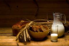Brocca di vetro con latte, tazza con latte, una pagnotta del pane di segale, orecchie Immagine Stock Libera da Diritti