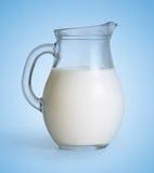 Brocca di vetro di latte sul blu fotografia stock libera da diritti