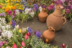 Brocche delle terraglie del contenitore dell'acqua dentro il letto di fiore Fotografia Stock