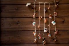 Brocche miniatura dell'argilla che pendono da una corda sulla parete di legno immagine stock libera da diritti