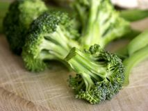 Broccoli. Cut up broccoli and used cutting board shallow dof stock photos