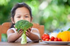 Broccoli asiatici della tenuta della ragazza del bambino ed imparare circa la verdura fotografia stock