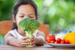 Broccoli asiatici della tenuta della ragazza del bambino ed imparare circa la verdura immagini stock