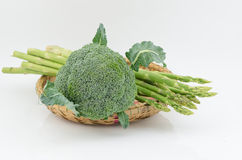 Broccoli and asparagus in basket. On white Stock Image