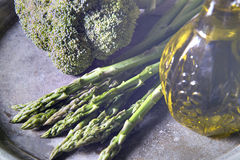 Broccoli, asparagus and olive oil. In a jug Royalty Free Stock Photo