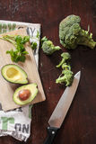 Broccoli and avocado with knife. Flatlay with broccoli, avocado and parsley on a dark brown wooden surface Stock Images