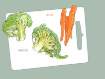 Broccoli and baby carrot . Cutting board and vegetables Royalty Free Stock Photos