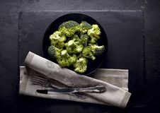 Broccoli on the black stone background. Top view stock images