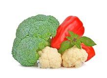 Broccoli, blomkål, röd peppar och basilika på vit Arkivbilder
