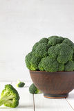 Broccoli in bowl with scattered bunch on the table. Fresh autumn vegetables for healthy diet Royalty Free Stock Image