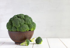 Broccoli in a brown bowl on a white wooden table. Stock Photos