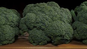 Broccoli cabbage on a wooden table. Dolly shot. Uncooked wet broccoli cabbage on a wooden table. Black background. Dolly shot stock video footage