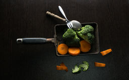 Broccoli and carrots food style in old pan on black wooden table Royalty Free Stock Photography