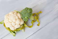 Broccoli and cauliflower on a wooden table with tape measure. Concept of weight loss and diet. Top view Royalty Free Stock Photography