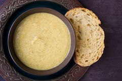 Broccoli and cheddar cheese soup. Fresh, home made broccoli and cheddar cheese soup served with a slice of sourdough bread on a stone slate table top Stock Photos