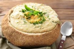 Broccoli cheddar soup in bread bowl. On wooden board stock images