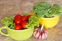 Broccoli, cherry tomatoes and garlic. Fresh broccoli, tomatoes in green and yellow bowls with garlic Royalty Free Stock Photography