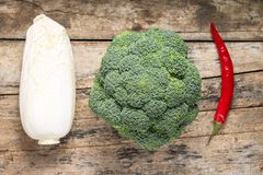 Broccoli, Chinesse Cabbage and Red Chilli Pepper on grunge wooden board Royalty Free Stock Photography