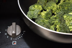 Broccoli Cooking. A pan has some raw broccoli in it and the stove knob is turned on to cook it Royalty Free Stock Image