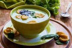 Broccoli creamy soup. Healthy food: broccoli creamy soup in a green bowl on the wooden background Stock Photo