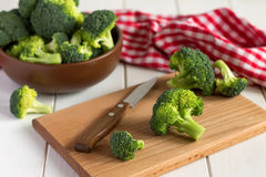 Broccoli on the cutting board with knife on a table. Fresh vegetables are a source of vitamins Royalty Free Stock Photo
