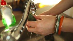 Broccoli di pulizia della donna in acqua sotto il rubinetto in lavandino stock footage